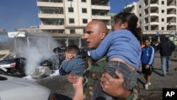 A Lebanese army soldier carries two injured children away from the site of an explosion near the Kuwaiti Embassy and Iran's cultural center, in the suburb of Beir Hassan, Beirut, Lebanon, Feb. 19, 2014.