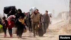 La gente carga sus pertenencias mientras huyen del enclave rebelde de Hammouriyeh, en el pueblo de Beit Sawa, Ghouta oriental, Siria, el jueves, 15 de marzo de 2018.
