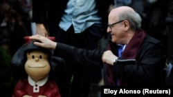 O cartoonista Joaquin Salvador Lavado, Quino, toca uma escultura de sua personagem cómica Mafalda, 23 outubro, Oviedo, Espanha