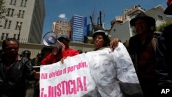 "FILE - Protesters hold a banner showing an image of Bolivia's former President Gonzalo Sanchez de Lozada that reads in Spanish ""Neither forget nor forgive, Justice!"" during a protest demanding his extradition outside the U.S. embassy in La Paz, Bolivia, Wednesday, Oct. 17, 2012."