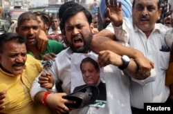 A demonstrator hits a poster of Pakistan's Prime Minister Nawaz Sharif during a protest organized by India's main opposition Congress party against Sunday's attack at an Indian army base camp in Kashmir's Uri in Jammu, India, Sept. 21, 2016.