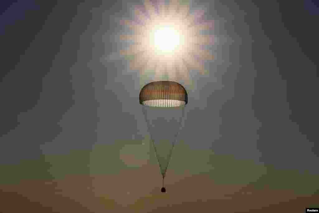 The Soyuz MS-03 capsule, carrying the International Space Station (ISS) crew of Oleg Novitskiy of Russia and Thomas Pesquet of France, is silhouetted against the sun as it descends beneath a parachute just before landing in a remote area outside Dzhezkazgan, Kazakhstan.