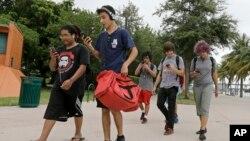 Sekelompok pemain Pokemon Go mengecek ponsel mereka sambil berjalan mencari Pokemon di Taman Bayfront, Miami, AS (12/7). (AP/Alan Diaz)