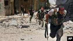 This Tuesday, July 9, 2013 citizen journalism image provided by Aleppo Media Center AMC, which has been authenticated based on its contents and other AP reporting, shows Syrian rebels running during heavy clashes with Syrian soldiers loyal to Syrian Presi