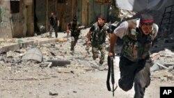 Tentara pemberontak Suriah berlari untuk menyelamatkan diri saat terjadinya bentrokan dengan pasukan loyal Presiden Assad, 9 Juli 2013 (AP Photo/Aleppo Media Center AMC).
