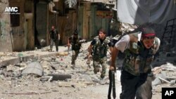 This Tuesday, July 9, 2013 citizen journalism image provided by Aleppo Media Center AMC, which has been authenticated based on its contents and other AP reporting, shows Syrian rebels running during heavy clashes with Syrian troops.