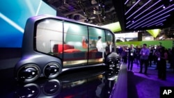 Attendees look at the Toyota e-Pallet concept at CES International, Tuesday, Jan. 9, 2018, in Las Vegas. (AP Photo/Jae C. Hong)