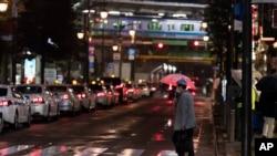 Seorang pria berjalan melintasi persimpangan jalan yang sepi, menuju stasiun kereta di Tokyo, Jumat, 5 Maret 2021. (AP Photo/Hiro Komae). Keadaan darurat untuk Tokyo dan sekitarnya diperpanjang hingga dua pekan mendatang.
