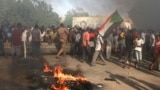 Sudanese men protest against a military coup that overthrew the transition to civilian rule, in the al-Shajara district in southern Khartoum, on October 25, 2021.