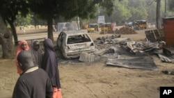 Des enfants deiscutent près du lieu d'une explosion au marché de Potiskum, Nigeria, le 12 janvier 2015.