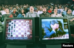 FILE - World chess champion Garry Kasparov rests his head in his hands as he is seen on a monitor during game six of the chess match against IBM supercomputer Deep Blue, May 11, 1997.