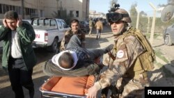 A wounded man is transported on a stretcher to receive treatment after a suicide bomb blast attack in Kirkuk, 250 km (155 miles) north of Baghdad, January 16, 2013.