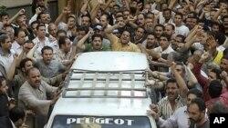 콥트 기독교인들이 무슬림과의 유혈충돌로 숨진 희생자의 운구차량을 둘러싸고 있다.