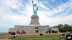 In this June 26, 2013 photo provided by the National Park Service, workers on Liberty Island install sod around the national monument which is set to re-open on the 4th of July, in New York.
