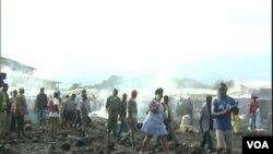 Les passants devant le marché de Limbe réduit en fumée, le 3 avril 2017