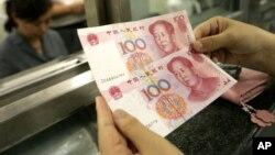 Seorang perempuan memegang mata uang China di sebuah bank di Beijing.