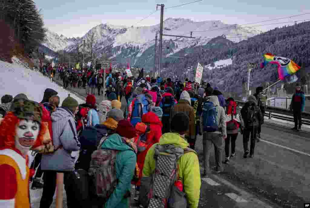صدها تن از معترضین به تغییرات اقلیمی در حال عبور از شهر کلُسترز به طرف داووس، سوئیس