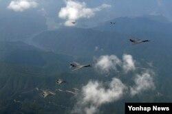 21일 괌에서 출격한 미국의 장거리 전략폭격기 B-1B 2대(가운데)가 주한미군 오산공군기지 상공에서 미군 F-16 전투기 2대(위), 한국군 F-15K 전투기 2대(아래)와 비행하고 있다.