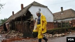 Seorang warga desa di kota kecil Kolontar, Hungaria melewati rumah-rumah yang terkena tumpahan limbah beracun.