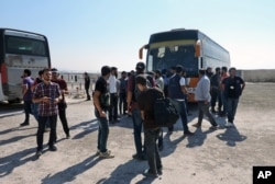 Rebels and their families arrive from the Damascus suburb of Daraya following a forced evacuation in Babiska, Idlib province, Syria, Aug. 27, 2016.