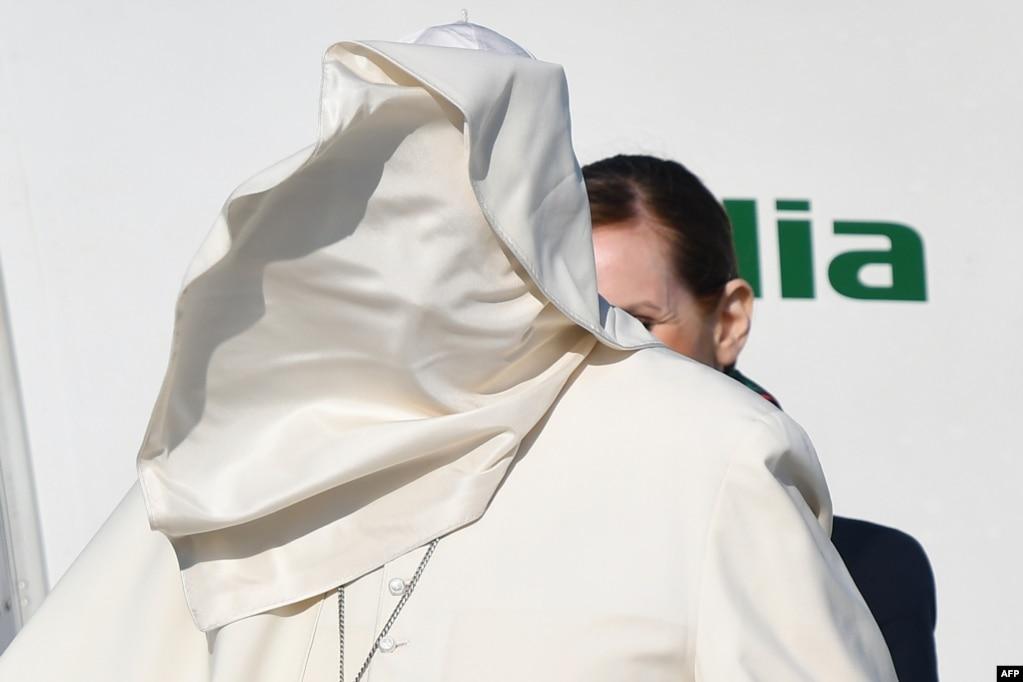 Порыв ветра поднимает рясу Папы Франциска на его лицо, когда он садится на самолет после его отъезда для трехдневной поездки в Румынию в римском аэропорту Фьюмичино, Италия.