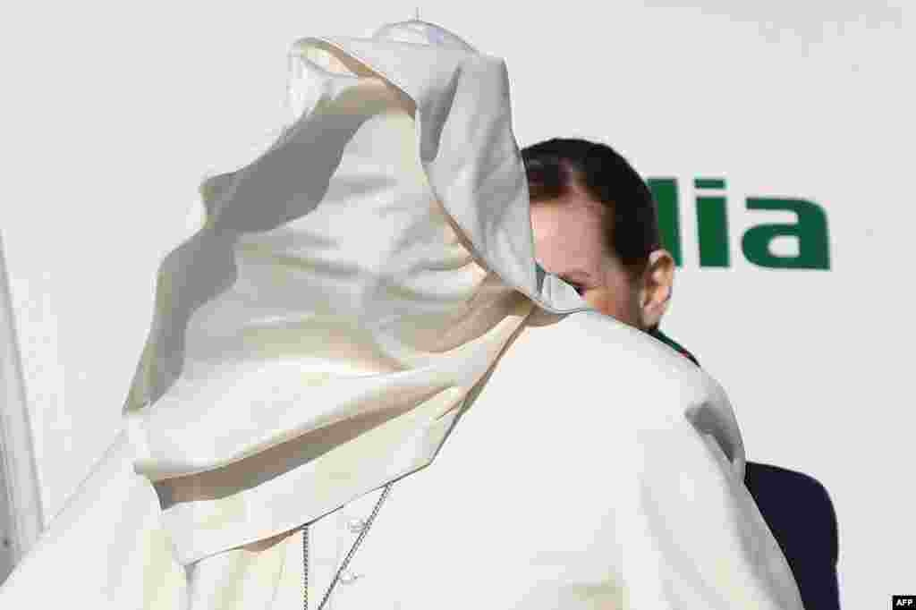 A gale of wind lifts Pope Francis' cassock upon his face as he boards a plane upon his departure for a three-day trip to Romania at Rome's Fiumicino airport, Italy.
