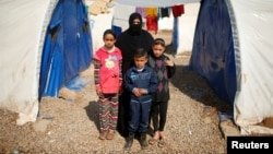 """Displaced Iraqi Orouba Abdelhamid, 31, poses for a photograph with her children at Hammam al-Alil camp south of Mosul, Iraq, April 1, 2017. Abdelhamid's husband, an engineer, was killed in a rocket strike as government forces arrived to expel Islamic State from her home city Mosul. """"No one is left for me over there so I came here... I cannot return to the house,"""" she said."""