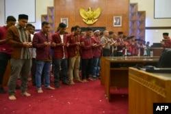 Para mahasiswa peserta demo dan pejabat kepolisi mendoakan korban unjuk rasa menentang berbagai RUU kontroversial, di ruang DPR Aceh, di Banda Aceh, 27 September 2019. (Foto: Chaideer Mahduddin/AFP)