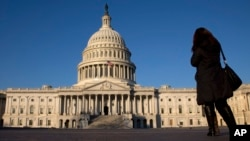 FILE - A woman walks past the U.S. Capitol in Washington.