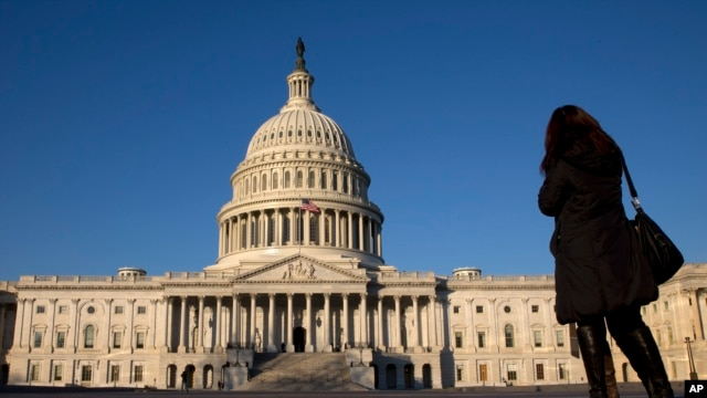 FILE - A woman looks at the U.S. Capitol in Washington. The White House says a bill that seeks to bar the U.S. from lifting certain sanctions against Iran would violate commitments necessary to implement the international agreement to limit the Iranian nuclear program.