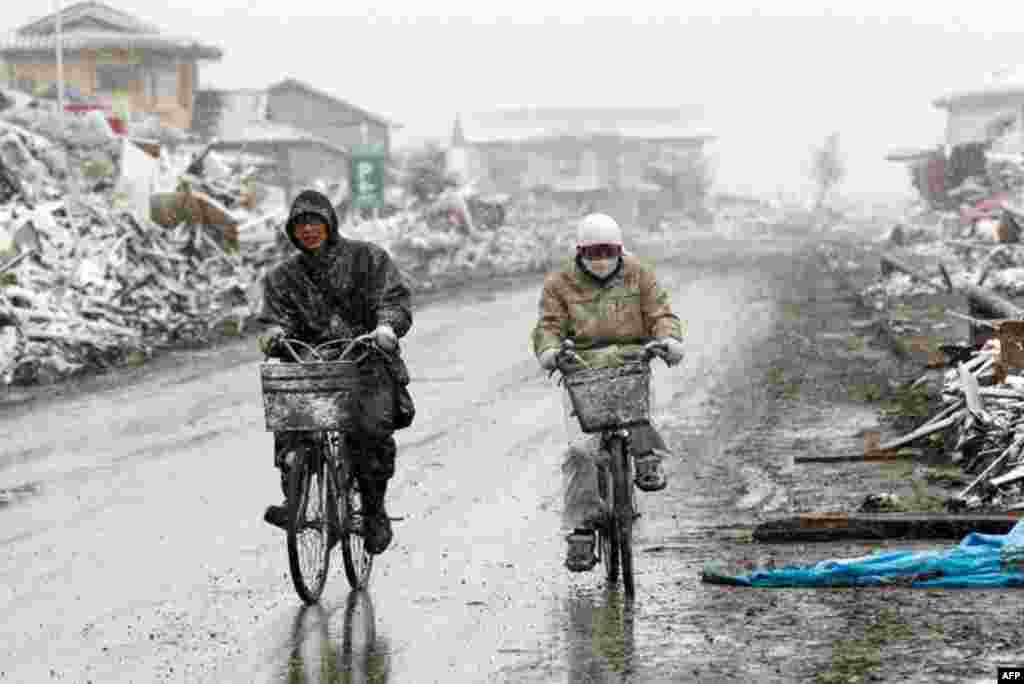 March 17: People ride bicycles past houses destroyed by an earthquake and a tsunami as snow falls in Natori City, Japan. (Reuters/Kyodo )