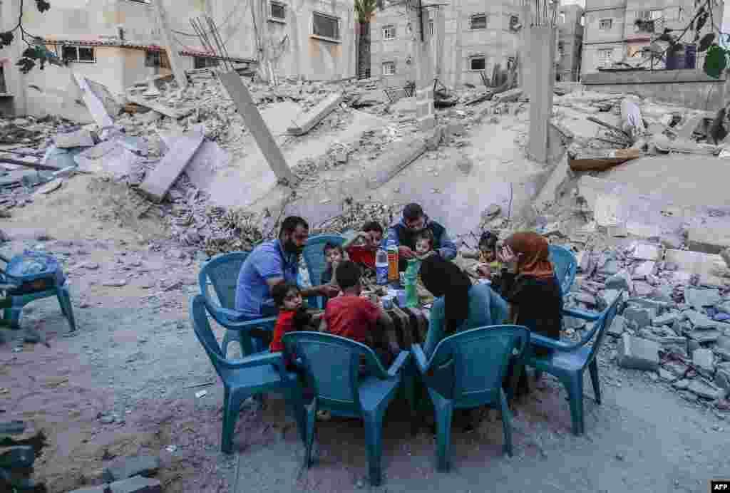 Keluarga Palestina berbuka puasa di samping rumah mereka yang hancur dalam konflik dua hari di Rafah, selatan Jalur Gaza, 8 Mei 2019. (Foto: AFP)