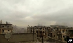In this still image taken from video released by a Syrian activist Wednesday smoke rises in the distance alongside the sound of heavy bombardment in east Aleppo, as a cease-fire deal to evacuate the city's residents begins to collapse. (Salah Ashkar via AP)