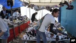 """地方政府债台高筑,可能殃及整体经济而导致""""崩盘""""。图为消费者4月15日在北京一个鞋市场挑便宜货"""