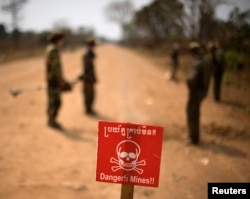 A sign warning of mines is placed on a road as Cambodian soldiers search for mines on the outskirts of Pailin, a former Khmer Rouge stronghold, in western Cambodia's Battambang province February 13, 2009. (Reuters)