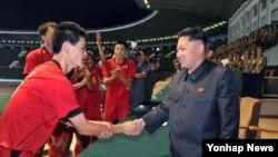 북한 김정은 국방위원회 제1위원장(오른쪽)이 '청년절'인 지난 8월 김일성 경기장에서 '횃불컵' 1급 남자축구 결승전을 관람하고 선수들과 인사하고 있다.