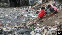Anak-anak bermain di tepi sungai yang dipadati sampah di Jakarta. (Foto: Dok)