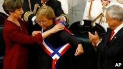 Michelle Bachelet recibe la banda presidencial de manos de la presidenta de la Cámara Alta, Isabel Allende Bussi. A la derecha aplaude el expresidente Sebastián Piñeira.