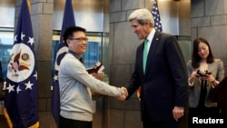 IBM employee Yang Bo shakes hands with U.S. Secretary of State John Kerry (2nd L) after being the first Chinese citizen to be issued a ten-year visa.