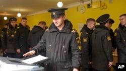 Un marinero militar ruso emite su voto durante la elección presidencial del domingo, 18 de marzo, de 2018, en Rusia.