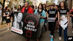 """Activists and journalists march to pay tribute to murdered journalist Pavel Sheremet, carrying a sign and wearing T-shirts that read """"Who killed Pavel?,"""" in Kyiv, Ukraine, July 20, 2017."""