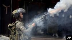 Seorang polisi Israel menembakkan gas air mata ke arah demonstran Palestina di kota al-Ram, utara Yerusalem, Kamis (22/10).