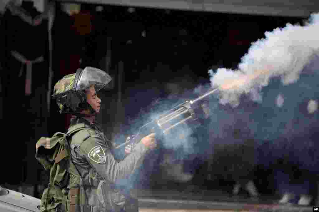 An Israeli policeman fires tear gas during clashes with Palestinian demonstrators in the West Bank town of al-Ram, north of Jerusalem. The violence erupted a month ago, fueled by rumors that Israel was plotting to take over a sensitive Jerusalem holy site revered by both Jews and Muslims.