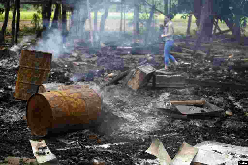 A journalist walks amongst the remains of houses at Shwe Lay village, outside of Thandwe in Rakhine state, western Burma, Oct. 2, 2013.