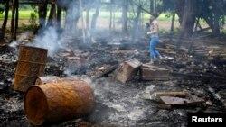 Seorang wartawan tengah berjalan di antara puing-puing rumah yang hangus terbakar di desa Shwe Lay, di pinggir wilayah Thandwe, negara bagian Rakhine, Burma (2/10).