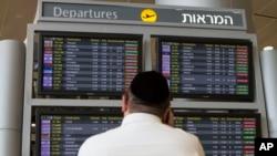 Tel Aviv havaalanında iptal edilen uçuk seferlerini inceleyen bir yolcu