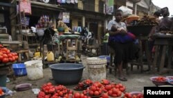 A woman waits for customer at a local food market, in Nigeria's commercial capital Lagos, January 16, 2012.