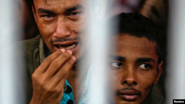 FILE - Rohingya people from Myanmar, who were rescued from human traffickers, react from inside a communal cell at Songkhla Immigration Detention Centre where they are kept near Thailand's border with Malaysia.