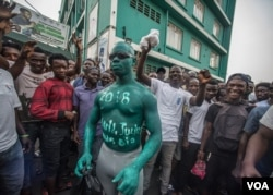 A supporter of Julius Maada Bio and the Sierra Leone People's Party wears green paint, the party's color, outside of SLPP headquarters in Freetown, Sierra Leone. (O. Acland/VOA)