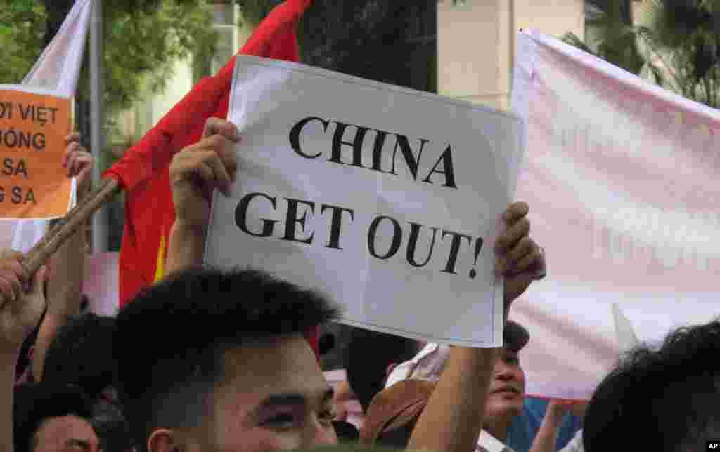 Người biểu tình cầm biểu ngữ phản đối việc Trung Quốc hạ đặt một giàn khoan dầu trong vùng lãnh hải tranh chấp ở Biển Đông.
